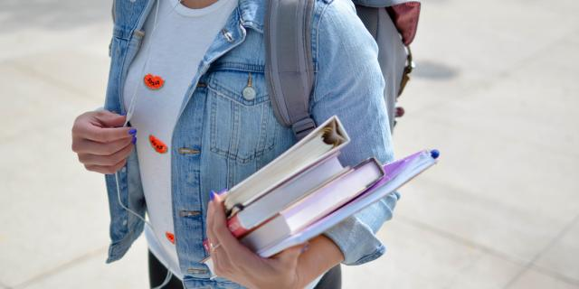 Girl carrying a backpack and books
